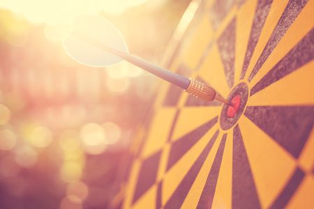 Close up blue dart arrow in the center of dartboard. Blur and bokeh in sunrise time background. Warm vintage effect style