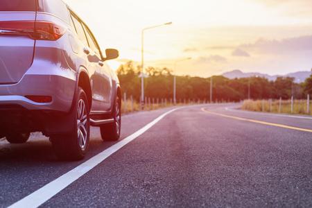 Mening van achterkant van nieuw zilveren SUV-autoparkeren op de asfaltweg in zonsondergangtijd Stockfoto