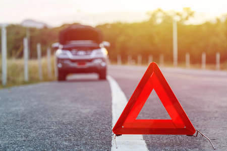 Red emergency stop sign and broken silver SUV car on the road Stock Photo