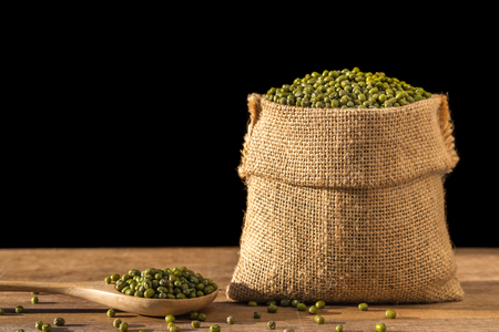 black gram: Close up of mung beans in small wooden sack on wooden table. Isolated on black background Stock Photo