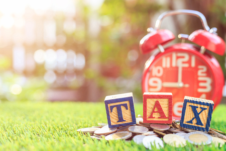 TAX write in color alphabet wood box on stack of Thai baht coin and red alarm clock with left free space for text. For time to pay tax concept. Shot in morning with sunlight and lens flare effect. Stock Photo