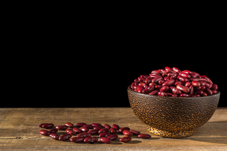Close up red bean in bowl on wooden table. Isolated on black background