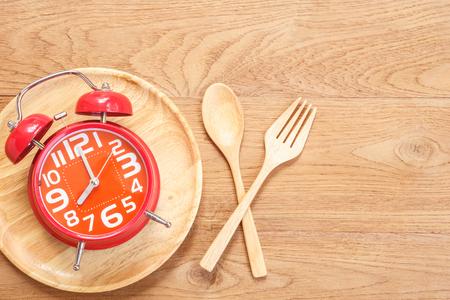 Hoogste menings rode wekker in houten schotel, lepel en vork op houten plankachtergrond. Tijd die concept eet Stockfoto