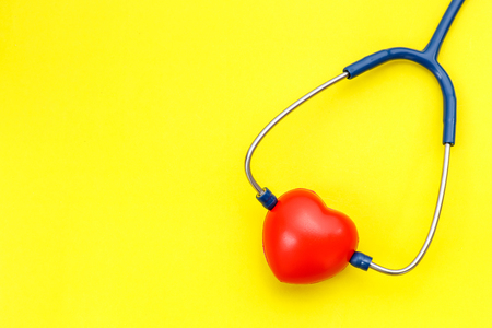 Top view blue stethoscope and red heart shape on yellow background. For check heart or health check up concept Stock Photo