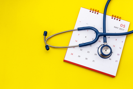 Top view blue stethoscope and white calendar on yellow background. Schedule to check heart or health check up concept
