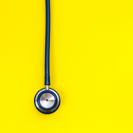 Top view blue stethoscope on yellow background. For check heart or health check up concept Stock Photo