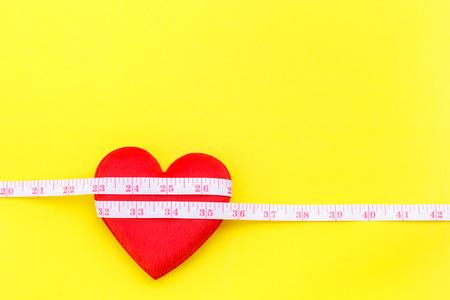 Vue de dessus forme de coeur rouge et ruban de mesure blanc sur fond jaune. Pour vérifier le c?ur ou vérifier le concept de taille