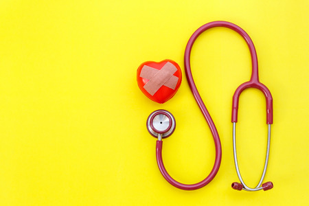 Top view red stethoscope and red heart shape on yellow background. For check heart or health check up concept