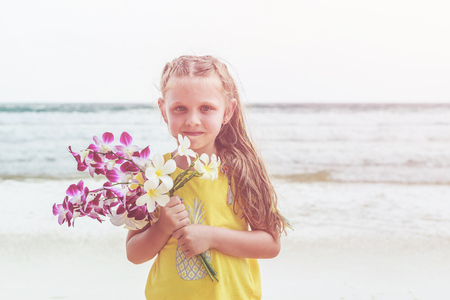 Caucasian little girl from europe holding orchid flower with happy and relax time on the tropical beach at Karon, Phuket province southern of Thailand