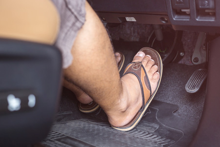 Close up right foot with flip flop shoe step on the brakes in the modern car