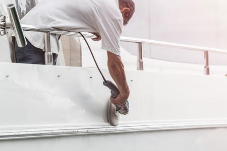 Jachtonderhoud. Een man polijsten kant van de witte boot door grinder machine in de jachthaven