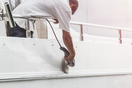 Yacht maintenance. A man polishing side of the white boat by grinder machine in the marina