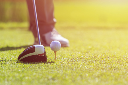 Golf player. A man playing golf in green course. Focus on golf ball