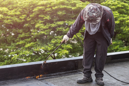 Asia worker installing tar foil on the rooftop of building. Waterproof system by gas and fire torching Stock Photo