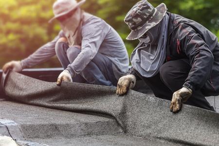 アジアの労働者の建物の屋上にタール箔をインストールします。ガスによるシステムの防水は、火をつけている火災