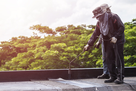 foil: Asia worker installing tar foil on the rooftop of building. Waterproof system by gas and fire torching Stock Photo