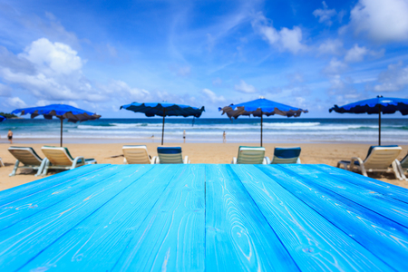 Empty free space of top blue wooden table and view of tropical beach background. For display or product montage design