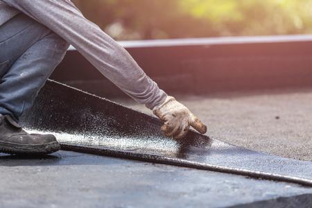 Trabajador de Asia que instala la hoja del alquitrán en el tejado del edificio. Sistema impermeable por incendio de gas y fuego Foto de archivo - 82419383