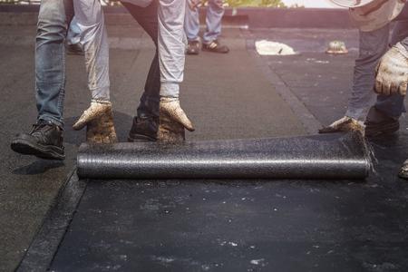 Travailleur asiatique installant du goudron sur le toit du bâtiment. Système imperméable à l'eau par torching à gaz et à incendie Banque d'images - 82397775