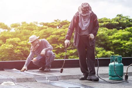 Lavoratore asiatico installando fogli di catrame sul tetto di costruzione. Sistema impermeabile per gas e fuoco a fuoco Archivio Fotografico - 82500574