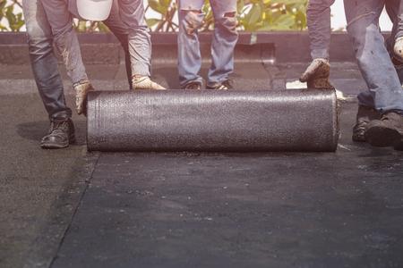Azië-arbeider installeren van tarfolie op het dak van het gebouw. Waterdicht systeem door gas- en brandlampen Stockfoto