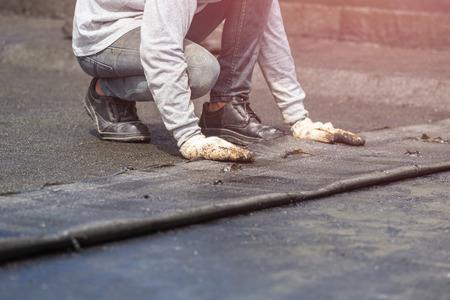 Asien Arbeiter Installation Teer Folie auf dem Dach des Gebäudes. Wasserdichtes System durch Gas- und Feuerbrenner