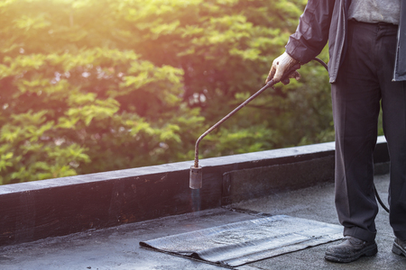 waterproofing material: Asia worker installing tar foil on the rooftop of building. Waterproof system by gas and fire torching Stock Photo