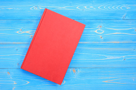 Top view old red book on wooden plank background. Blank empty cover for design Standard-Bild