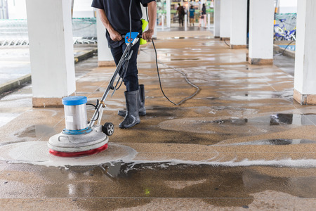 Asian worker cleaning sand wash exterior walkway using polishing machine and chemical or acid 免版税图像 - 84928903
