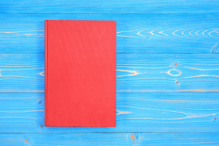 Top view old red book on wooden plank background. Blank empty cover for design Stock Photo