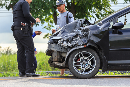KAMPHAENG PHET, THAILAND - JULY 17 : An unidentified people checking front of black car which got damaged by accident on the road on July 17, 2017 in Kamphaeng Phet, Thailand.