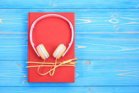 audio book: Top view book and new modern pink music headphone on blue wooden plank background. With space for text or design.
