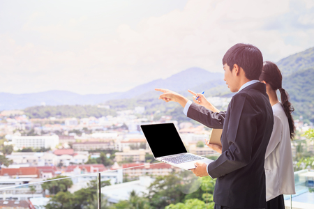 Portrait young asian businessman standing at the terrace looking to building and property. Used for real estate concept