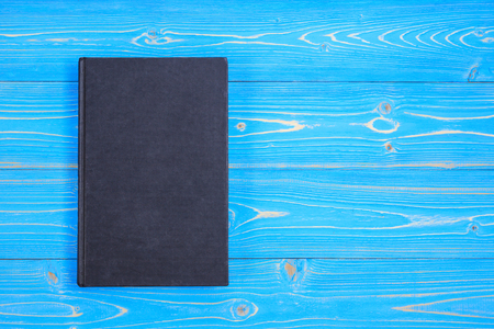 Top view old black book on wooden plank background. Blank empty cover for design Stock Photo
