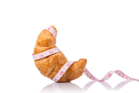 Close up Croissant and measurement tape. Studio shot isolated on white background. Junk food, obesity or food healthy concept