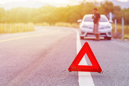 Red emergency stop sign and broken silver car on the road Stock Photo
