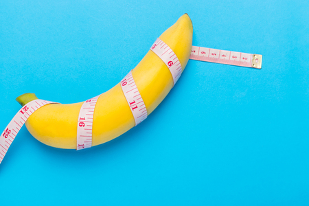 educacion sexual: Close up yellow banana with measurement tape on blue background. Men penis size concept with empty free space for text or design. Top view Foto de archivo