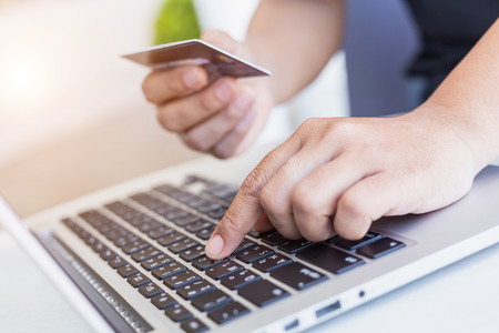 Close up woman hands holding credit card in front of laptop on the desk. Easy way online shopping concept
