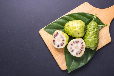Fruit of Great morinda (Noni) or Morinda citrifolia tree and green leaf on black stone board background Standard-Bild