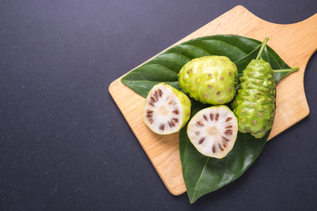 Fruit of Great morinda (Noni) or Morinda citrifolia tree and green leaf on black stone board background Stock fotó