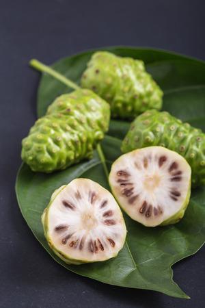 Fruit of Great morinda (Noni) or Morinda citrifolia tree and green leaf on black stone board background Stock Photo