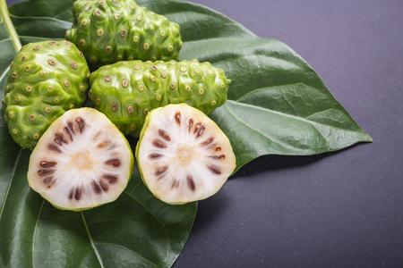 Fruit de Great morinda (Noni) ou arbre de Morinda citrifolia et feuille verte sur fond de panneau de Pierre noir Banque d'images - 88366255