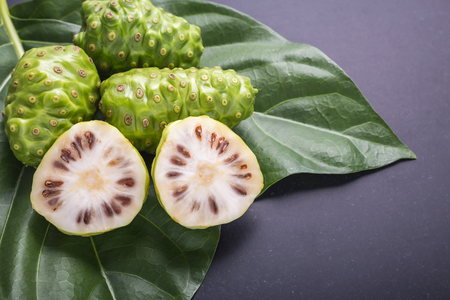 Fruit of Great morinda (Noni) or Morinda citrifolia tree and green leaf on black stone board background Archivio Fotografico