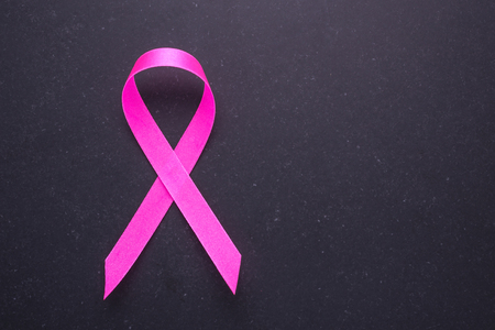 Breast Cancer concept : Pink ribbon symbol of breast cancer on black stone background