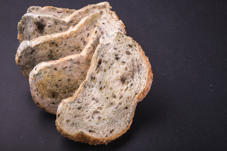 Mold on bread put on black stone table background. Top view Stock Photo