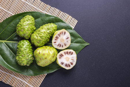 Fruit of Great morinda (Noni) or Morinda citrifolia tree and green leaf on black stone board background Stock Photo