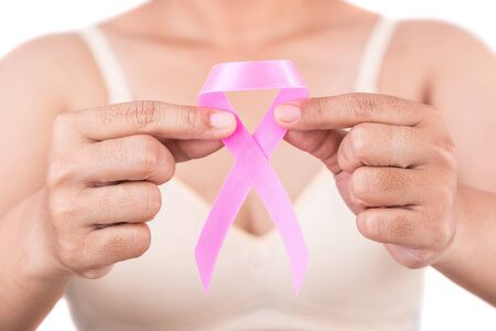 Breast Cancer concept : Woman holding pink ribbon symbol of breast cancer isolated on white background