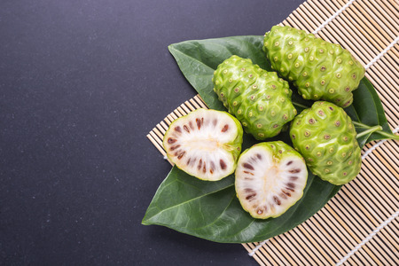 Fruit of Great morinda (Noni) or Morinda citrifolia tree and green leaf on black stone board background Stok Fotoğraf