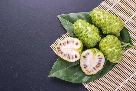 Fruit of Great morinda (Noni) or Morinda citrifolia tree and green leaf on black stone board background Stockfoto