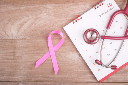 Breast Cancer concept : Pink ribbon symbol of breast cancer, calendar and stethoscope on brown wooden table background. For breastbody checking appointment